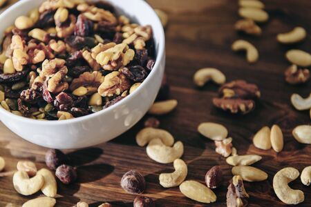 white bowl with mixed nuts on rustic wooden table, healthy food and snack concept