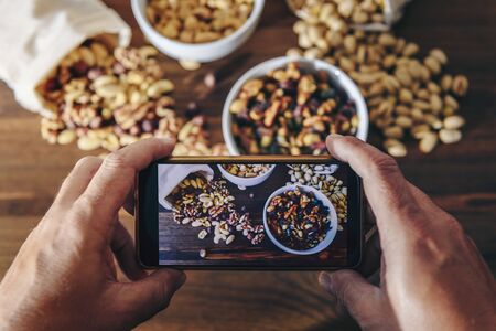 food blogger takes photo for blog, pic of selection of varied nuts and dried fruit in bowls and cloth sacks on a wooden table, healthy food concept and vegetarian snack, selective focus Banco de Imagens