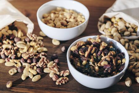 selection of mixed nuts and dried fruit in white bowls and burlap sack on a wooden table, healthy food and snack concept