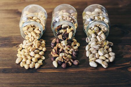 three glass jars with varied nuts and mixed dried fruits inside on a rustic wooden background throwing their contents on the table, healthy food and snack concept