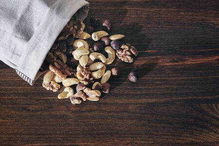 mix of nuts and dry fruits in burlap bag on wooden background, healthy food and snack concept, copy space for text