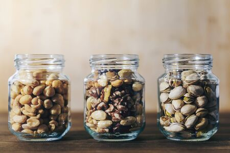 three glass jars with mixed nuts and dried fruits inside on a rustic wooden table, healthy food and snack concept, copy space for text