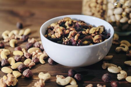 white bowl with organic mixed nuts on rustic wooden table, healthy food and snack concept, copy space for text