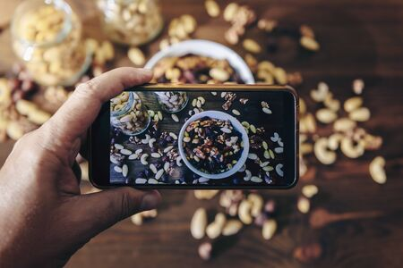 food blogger takes photo for blog, pic of a white bowl with varied organic dry fruits and glass jars with mixed nuts on rustic wooden table, healthy food and vegan snack concept, selective focus
