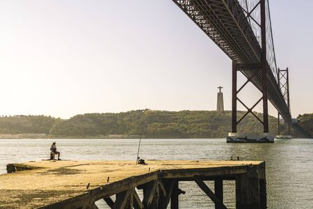 unrecognizable man fishing in the Tagus river under the 25 de Abril bridge in Lisbon, Portugal. On the other bank is the monument of Cristo Rei (Christ the King)