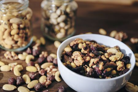white bowl with varied organic dry fruits and glass jars with mixed nuts in the background on rustic wooden table, healthy food and snack concept, copy space for text