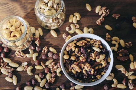 top view of a white bowl with varied organic dry fruits and glass jars with mixed nuts on rustic wooden table, healthy food and snack concept