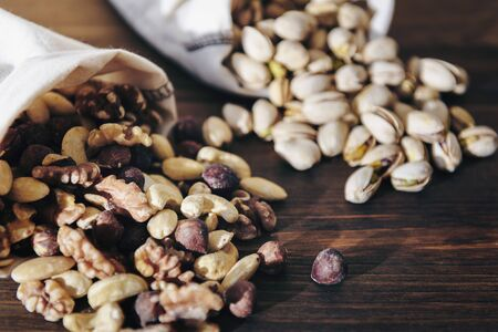 mixed nuts, pistachios and dry fruits in burlap bags on wooden table, healthy food and snack concept Banco de Imagens