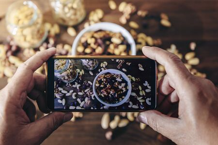 food blogger taking photo for blog, pic of a white bowl with varied organic dried fruits and glass jars with mixed nuts on a wooden table, healthy food and vegan snack concept, selective focus