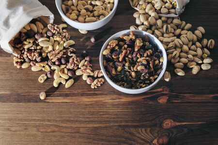 selection of varied nuts and dried fruit in white bowls and burlap sacks on a wooden table, healthy food concept, copy space for text