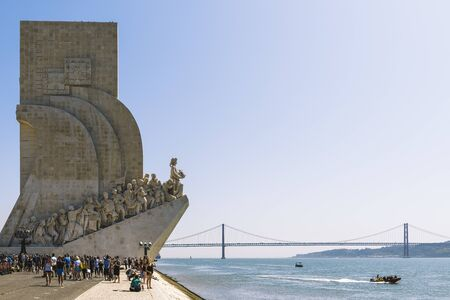 Lisbon, Portugal – august, 2019. Tourists at the monument to the Discoveries in Lisbon, is on the banks of the Tagus river and in the background you can see the 25 de Abril (25 April) bridge Banco de Imagens