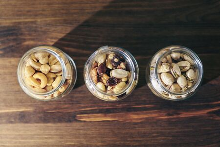 top view of three glass jars with mixed nuts and dried fruits inside on a rustic wooden table, healthy food and snack concept, copy space for text Banco de Imagens