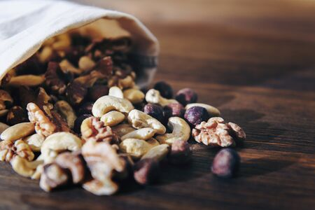 mix of nuts and dry fruits in burlap bag on wooden table, healthy food and snack concept, copy space for text