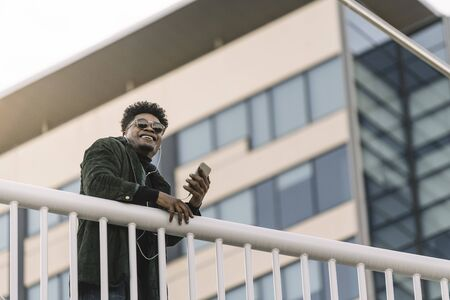 portrait of a smiling young black man with sunglasses listening to music with earphones and mobile phone while leaning on a handrail outdoors in the city, technology and lifestyle concept