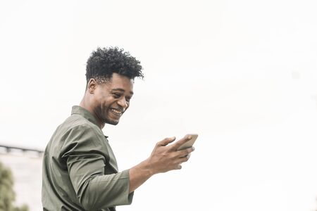 portrait of a cool young african black man texting a message and looking the phone in white background, lifestyle and technology concept, copy space for text