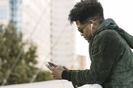 cool young african black man with sunglasses and earphones texting message on smartphone while leaning on a handrail outdoors in the city, lifestyle and technology concept, copy space for text Banco de Imagens