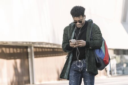 black young man with earphones walking by the city and texting with a mobile phone, technology and lifestyle concept using internet electronic device outdoors