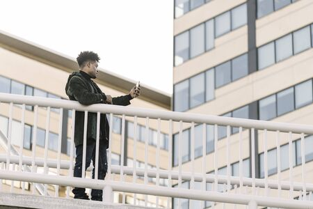 serious african black man with earphones making video call with a mobile phone leaning on a handrail outdoors in the city, technology and lifestyle concept using internet electronic device Banco de Imagens
