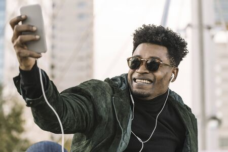 handsome young african black man with sunglasses making a video call with smartphone and earphones while sitting in the city, lifestyle and technology concept using internet electronic device