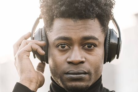 portrait of a serious african black man listening music with a hand touching the headphones at sunset, technology and lifestyle concept Banco de Imagens