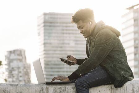 handsome young student with white earphones and phone working typing in a computer sitting outdoors in the city at sunset, lifestyle and technology concept using internet electronic device Banco de Imagens
