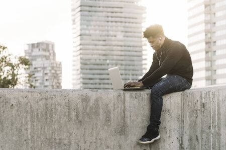 handsome black man with white earphones working typing in a computer sitting outdoors in the city at sunset, lifestyle and technology concept using internet electronic device Banco de Imagens