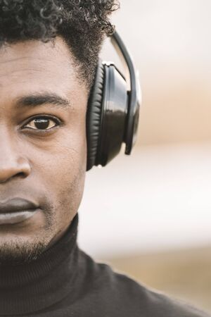 vertical half head portrait of a serious african black man listening music with the headphones, technology and lifestyle concept