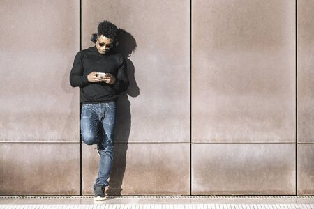 cool african black man with casual modern clothes and headphones listening music of his phone leaning against wall, technology and lifestyle concept
