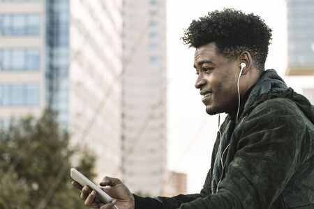 cool young african black man with white earphones and smartphone in the hand outdoors in the city, lifestyle and technology concept, copy space for text