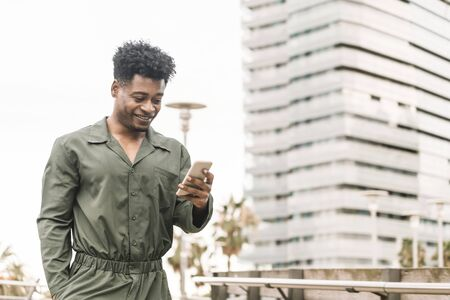 stylish young african black man smiling and texting message on the phone while walks in a park outdoors in the city, lifestyle and technology concept, copy space for text Banco de Imagens