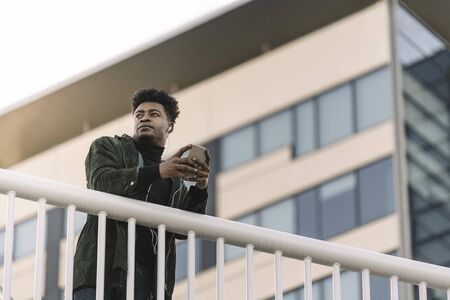 portrait of a young cool african black man listening to music with earphones and mobile phone while leaning on a handrail outdoors in the city, technology and lifestyle concept