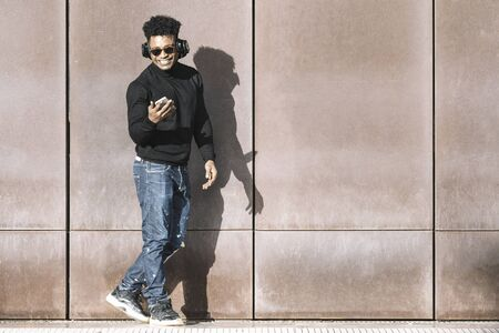 cool african black man with casual modern clothes and headphones listening music of his phone walking smiling in front of a wall, technology and lifestyle concept
