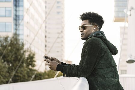 cool young african black man with sunglasses listening music on smartphone with earphones while leaning on a handrail outdoors in the city, lifestyle and technology concept, copy space for text