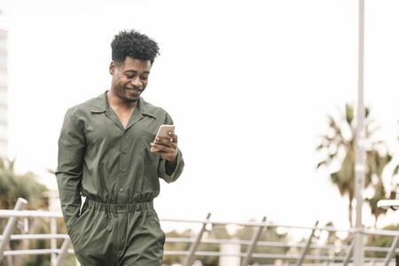 handsome young african black man smiling and texting message on smartphone while walks in a park outdoors in the city, lifestyle and technology concept, copy space for text Banco de Imagens