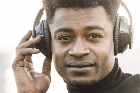 portrait of a happy african black man smiling listening music with a hand touching the headphones at sunset, technology and lifestyle concept