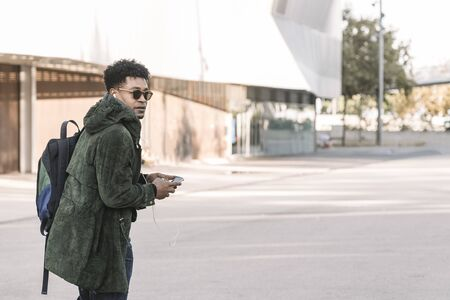 african american young male with earphones walking by the city and listening music with a mobile phone, technology and lifestyle concept using internet electronic device outdoors
