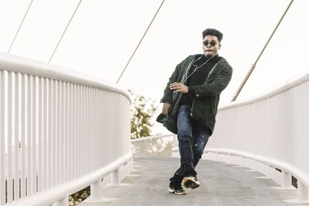 young stylish black guy with white earphones and sun glasses walking outdoor in the city, dancing happy and having some fun, lifestyle and technology concept, copy space for text