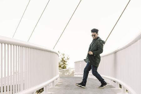 young stylish black man with white earphones and sun glasses dancing happy outdoor in the city and having some fun, lifestyle and technology concept, copy space for text