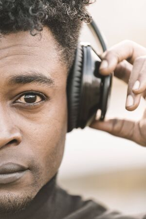 vertical half head portrait of a serious african black man listening music with a hand touching the headphones, technology and lifestyle concept