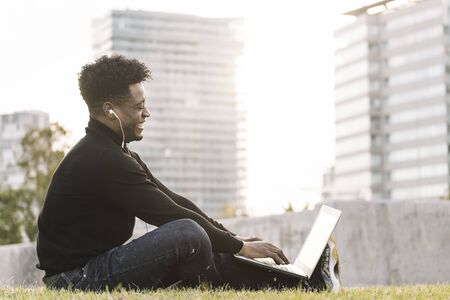 smiling young black student laughing with earphones making a video call with the computer sitting on the lawn in the city at sunset, lifestyle and technology concept using internet electronic device Banco de Imagens
