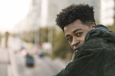 attractive young black african man with green jacket listening music with white earphones, city lifestyle concept
