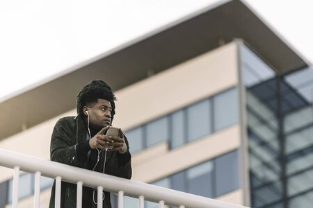 portrait of a smiling young attractive african black man listening to music with earphones and mobile phone while leaning on a handrail outdoors in the city, technology and lifestyle concept