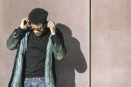 cool african black man with casual modern clothes and headphones listening music leaning against wall, technology and lifestyle concept Banco de Imagens