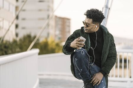handsome young african black man with sunglasses listening music on smartphone with earphones while sitting in the city, lifestyle and technology concept, copy space for text Banco de Imagens