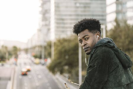 attractive young black african man with green jacket listening music with white earphones in the city, lifestyle concept Banco de Imagens