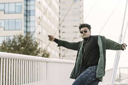 young handsome african black man with white earphones and sun glasses having fun and dancing outdoor in the city, lifestyle and technology concept, copy space for text