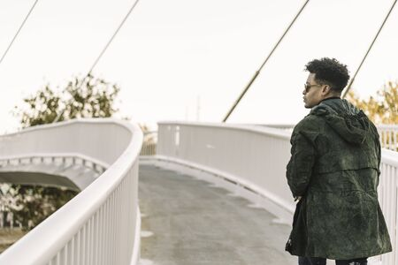 view from behind attractive young black african man with cool casual wear and sunglasses walking on a modern bridge in the city, lifestyle concept