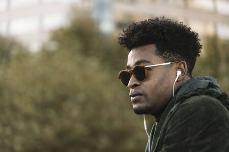 handsome young black african man with green jacket and sunglasses listening music with white earphones, city lifestyle concept