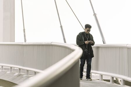 black man walks around looking at his smartphone while listen music in earphones in the city, technology and lifestyle concept using internet electronic device