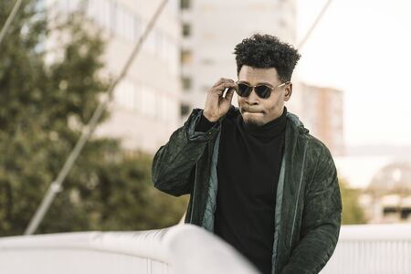 handsome young african black man with green jacket and sunglasses walking by the city, lifestyle concept